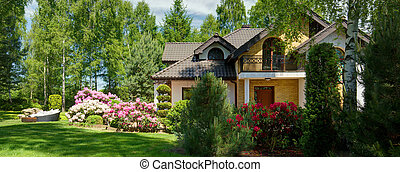 Panoramic view of luxurious villa with secluded blooming garden