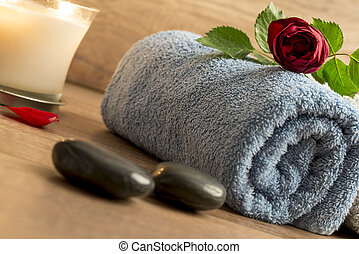 Luxurious wellness arrangement with a rolled blue towel, red rose, burning candle, and two black massage stones