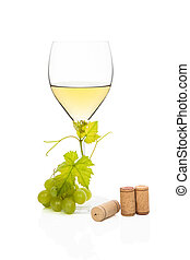 White wine in wine glass with green grapes, vine leaves and various wine corks isolated on white background. Luxurious wine still life.
