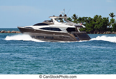 Luxury Afloat - Black yacht powering across the Florida...