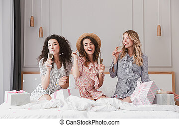 Luxury bachelorette party in posh apartment, while beautiful excited three women 20s having fun and drinking champagne