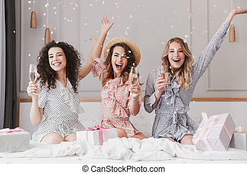 Luxury bachelorette party in posh apartment while happy young three women 20s having fun, and drinking champagne under falling confetti