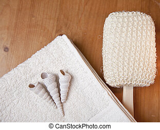 Luxury bath or shower set with towel, brush and shells on wooden background