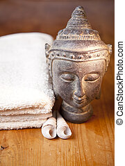 Luxury bath or shower set with towel, buddha and shells on wooden table