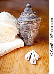 Luxury bath or shower set with towel, sponge and buddha and shells on wooden table