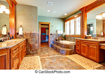 Luxury bathroom with tile wall trim and tile floor. View of vanity with mirror and bath tub with step