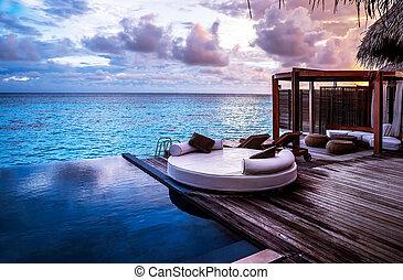 Luxury beach resort, bungalow near endless pool over sea...