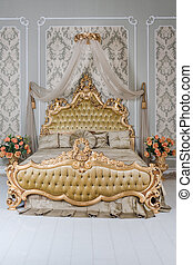 Luxury bedroom in light colors with golden furniture details. Big comfortable double royal bed in elegant classic interior