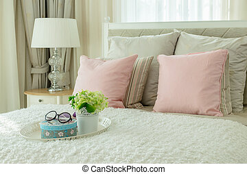 luxury bedroom interior with pink pillows and white tray of flower on bed