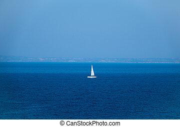 luxury big sailing boat at the horizon on open sea.