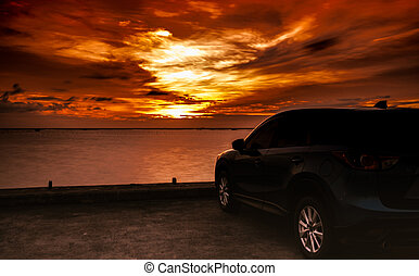 Luxury blue SUV car parked on concrete road by the sea at sunset with dramatic sky and clouds. Electric car technology and business. Hybrid auto and automotive industry. Tropical road trip travel.