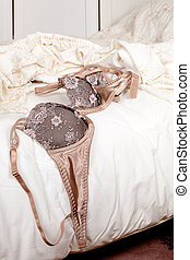 Luxury lace bra and thong lying on a messy bed