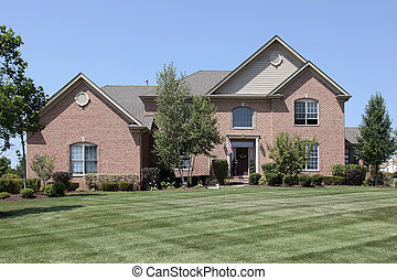 Luxury brick home in suburbs with manicured lawn