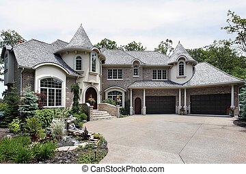 Front view of luxury brick home with two turrets