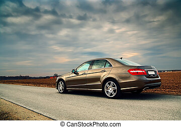 Luxury car - Rear view of a luxury car on country road with...