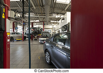 Luxury cars being repaired in a modern garage. View through...