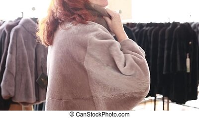Luxury clothes and furs in a retail fashion store. - Mink...