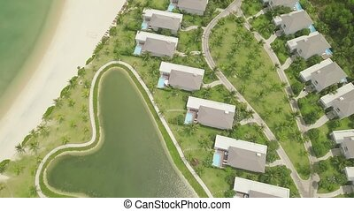 Luxury cottage village with houses, swimming pool and lakes on sea shore aerial view. Drone view tourist resort villas on green lawn and lake background.