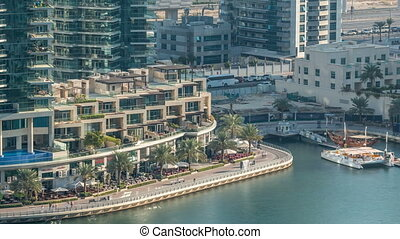 Luxury Dubai Marina canal with passing boats and promenade...