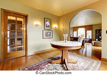 Luxury entrance home interior with round table and hardwood floor.