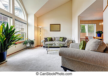 Luxury family room in soft creamy tones with hight ceiling and a