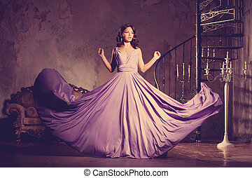 Luxury fashion stylish woman in the rich interior. Beautiful girl with a fashionable hairstyle and makeup chic