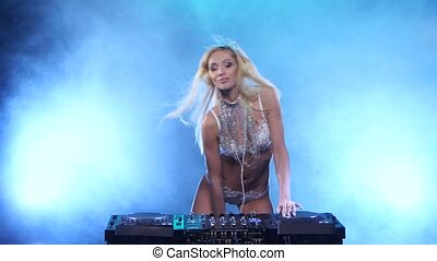 Luxury girl DJ in white lingerie dances for mixing console