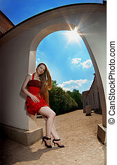 Luxury girl in a red dress against the sun