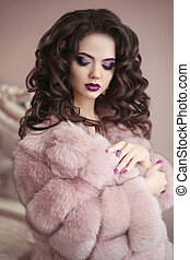 Luxury girl in pink fur coat. Beauty makeup. Brunette with long curly hairstyle, elegant fashion glamour woman. Beautiful lady portrait.
