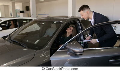 Luxury girl sitting behind the wheel of a new car in the car dealership. Car sale