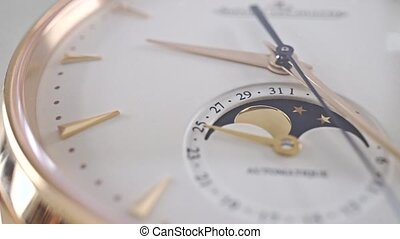 Luxury golden wrist watch with phase of the Moon indicator. Macro dolly shot
