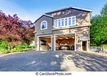 Luxury gray house with white trim and two motor boats in garage.