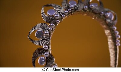luxury headband with small silver wings pearls and shiny metal ribbons turns on brown background extreme close view