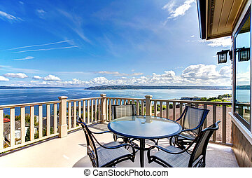 Luxury home balcony deck with water view and table.
