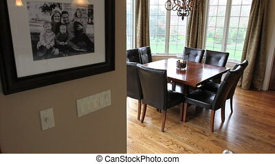 Moving dolly shot of a breakfast nook table and chairs surrounded by large windows in a luxury home, with a family portrait on the wall