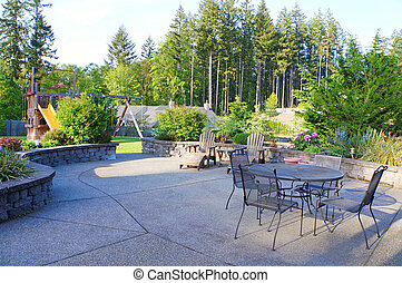 Luxury home large back yard with furniture and play gorund area with stone walls.