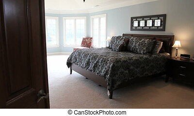 Moving dolly shot of a large master bedroom in a luxury house