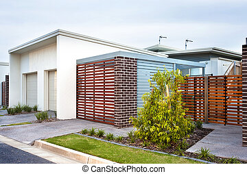 Luxury house front side with wooden gate and garden