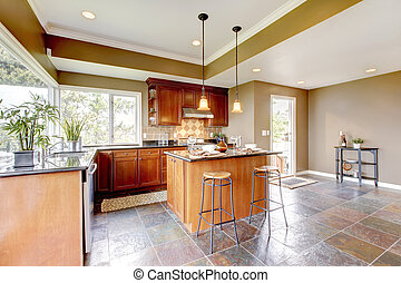 Luxury kitchen interior with green walls and stone floor.