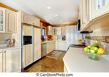 Luxury kitchen with cream cabinets, and white counter tops.