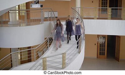 Luxury ladies cute talking and go down for huge staircase in an expensive country house. Beautifully dressed girls difficult to walk in high heels on the stairs.