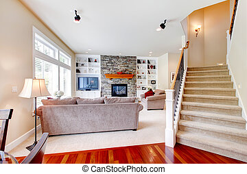 Luxury large beige living room with staircase.