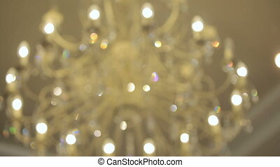 Luxury large crystal chandelier hanging. Vintage lighting lamps with light bulbs and a lot of pendants.