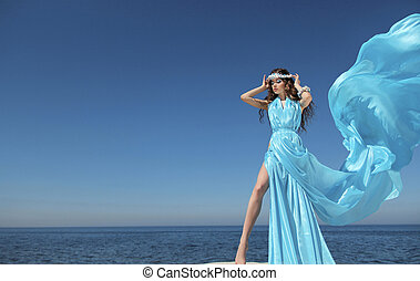 Luxury life. Fashion model girl with blowing tissue dress...