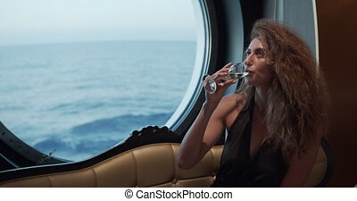 Luxury lifestyle - Woman drinking champagne. Elegant lady holding wine glass and looking on window over the ocean enjoying amazing view on luxury vacation..