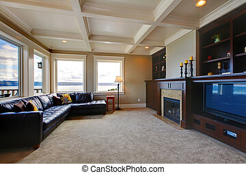 Large luxury living room wth TV, water view, and shelves.