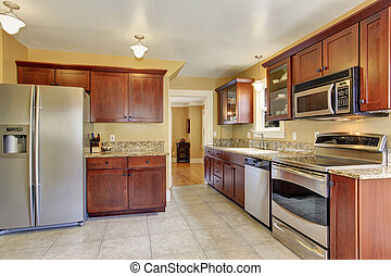 Luxury modern kitchen with stained cabinets, and stainless steel fridge.