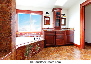 Luxury new home bathroom with red marble and mahogany wood.