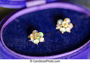 luxury opal and pink opal in a purple and blue jewelry case.