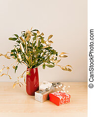 Luxury packed gifts in red and silver with mistletoe in vase